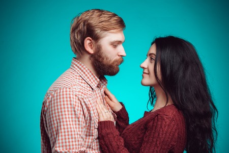 The embrace of young man and woman on blue studio background
