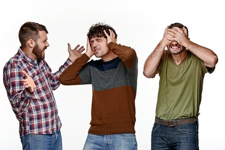 The young three men standing on white studio background with different puzzled emotions Stock Photo
