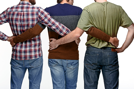 backs: United backs of friends of business men standing in embrace and on white studio background