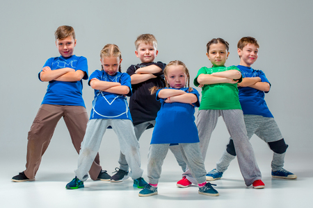 Los niños bailan la escuela, ballet, hip-hop, calle, funky y bailarines modernos en fondo gris del estudio Foto de archivo