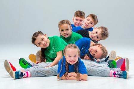 Die Kinder tanzen Schule, Ballett, Hip-Hop, Street, funky und moderne Tänzer auf grauem Hintergrund Studio