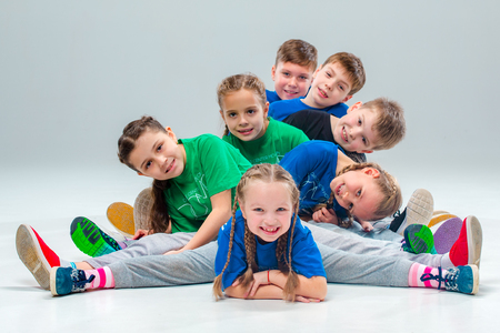 The kids dance school, ballet, hiphop, street, funky and modern dancers on gray studio background Stok Fotoğraf