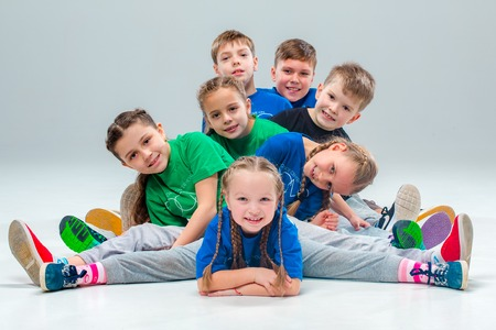 The kids dance school, ballet, hiphop, street, funky and modern dancers on gray studio background Фото со стока