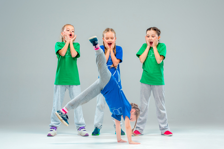 The kids dance school, ballet, hiphop, street, funky and modern dancers on gray studio background Stock Photo