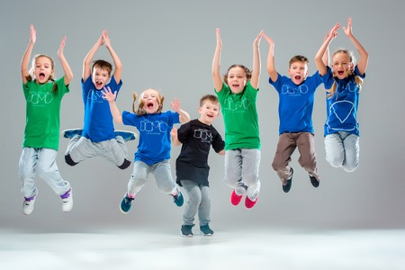 The kids dance school, ballet, hiphop, street, funky and modern dancers on gray studio background Stock fotó