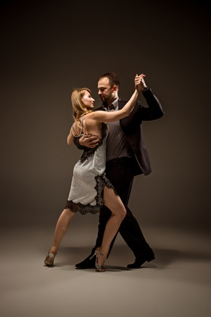 A man and a woman dancing argentinian tango on gray studio background Stock Photo - 67225840
