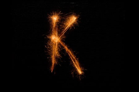 The English letter K made of sparklers on black background