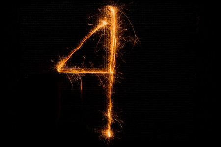 The number 4 made of sparklers on black background