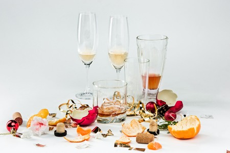 The morning after christmas day, table with alcohol and leftovers from a celebratory feast on gray Stock Photo