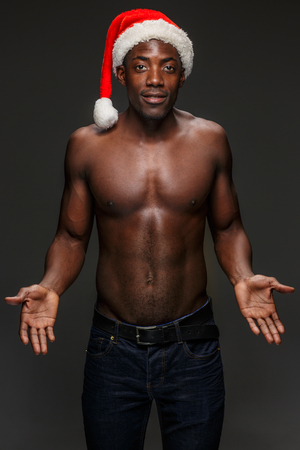 something athletic: Muscular black shirtless young man in Santa Claus hat standing on white studio background and showing something Stock Photo