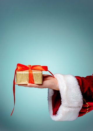 xmass: The hand of santa claus holding a gift on blue background Stock Photo