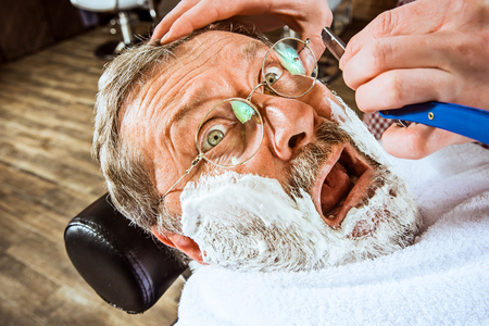 The emotional senior man visiting hairstylist in barber shop Stock Photo