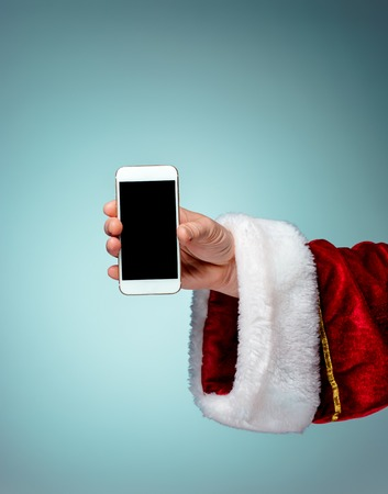 Santa Claus holding mobile phone ready for Christmas time on blue studio background Stock Photo