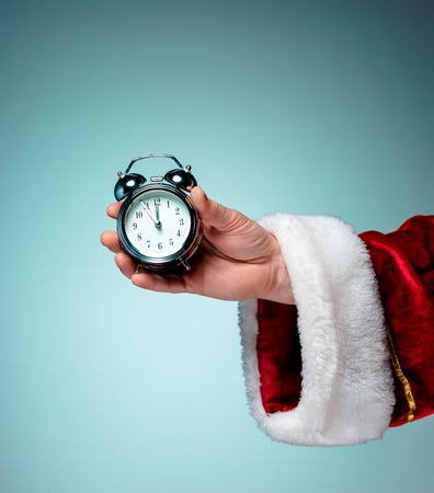 Santa holding an old alarm clock on blue background Stock Photo