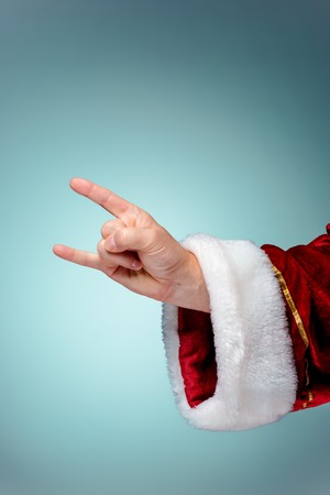 xmass: Photo of Santa Claus hand in rocker gesture on blue Stock Photo