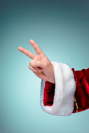 raise the thumb: Santa Claus hand showing sign victory by thumbs up on blue background