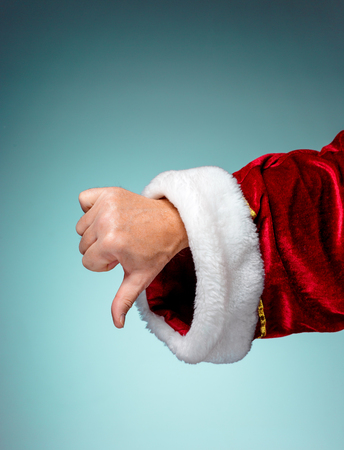 Photo of Santa Claus hand in pointing gesture on blue