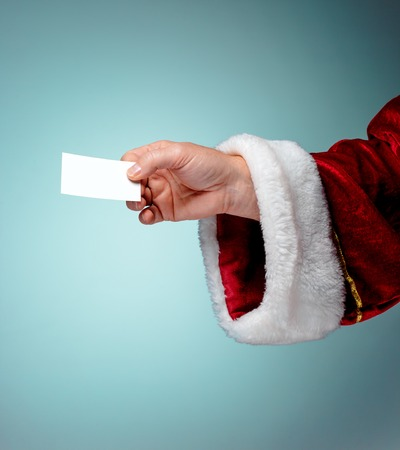 xmass: Photo of Santa Claus hand with a business card on blue Stock Photo