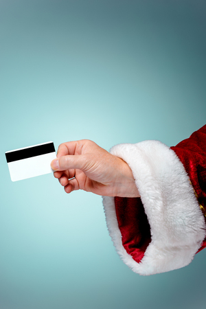 xmass: Santa Claus hand holding a credit card on blue studio background