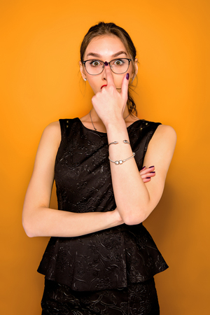 Portrait of young woman with glasses and shocked facial expression on orange studio background Stock Photo