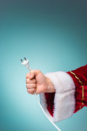 electrical plug: The hand of santa claus holding a electrical plug to gadgets on blue background Stock Photo