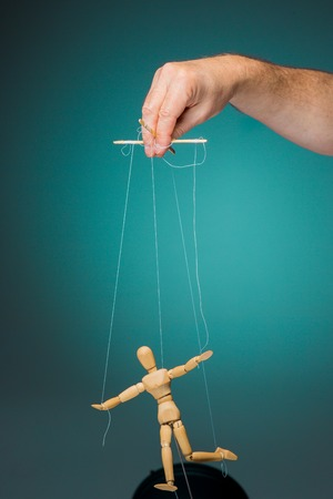 puppet master: Image puppet in the hands of the puppeteer on blue background
