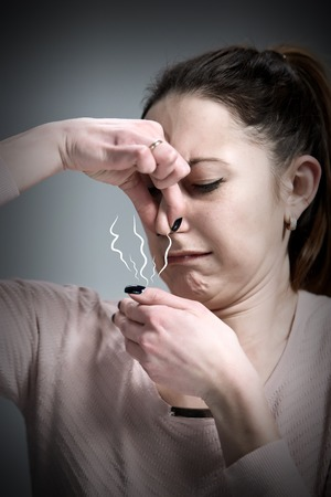 disgusted: The portrait of disgusted woman on gray. concept odor