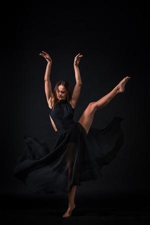 Young beautiful dancer in beige dress dancing on black studio background Stock Photo