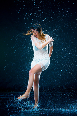 rain wet: The young girl standing under running water Stock Photo