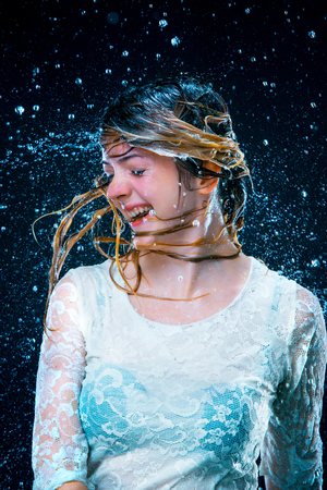 The young girl standing under running water Stock Photo