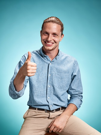 excite: Happy excite young man smiling over blue background