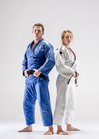 The two judokas fighters posing on gray Stock Photo