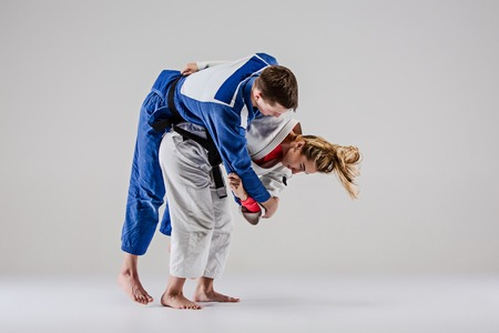 The two judokas fighters posing on gray Banque d'images