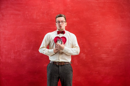 constraining: Young funny man with abstract heart and clock