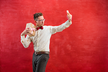 constraining: Young beautiful man with gift and phone Stock Photo