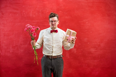 constraining: Young funny man with flowers and gift