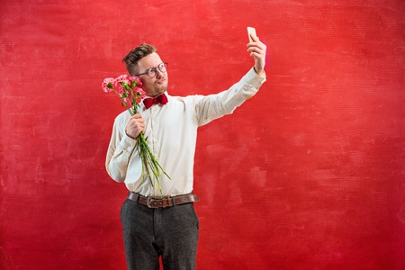 constraining: Young beautiful man with flowers and phone Stock Photo