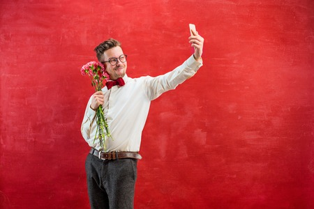 Young beautiful man with flowers and phone Stock Photo