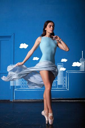 modern ballet dancer: The modern ballet dancer posing on blue city background