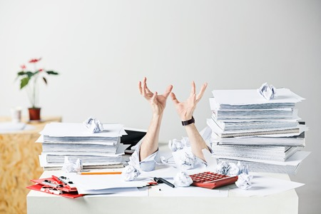 The many crumpled papers on desk of stressed male workplace Imagens