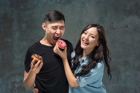 pareja asiática joven disfrutar de comer de rosquilla colorido dulce