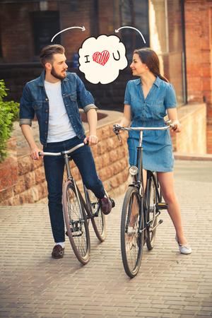parejas enamoradas: Pareja joven sentado en una ciudad, frente a la bicicleta