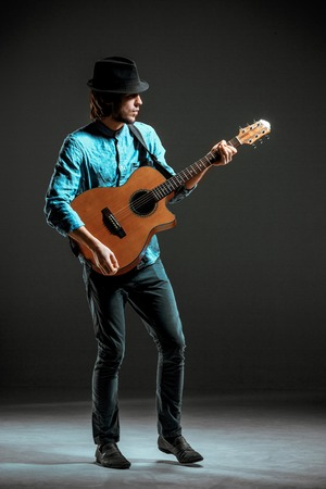 hombre sentado: Cool guy standing with guitar on dark background