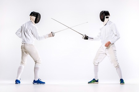 The two men wearing fencing suit practicing with sword against gray Stock Photo