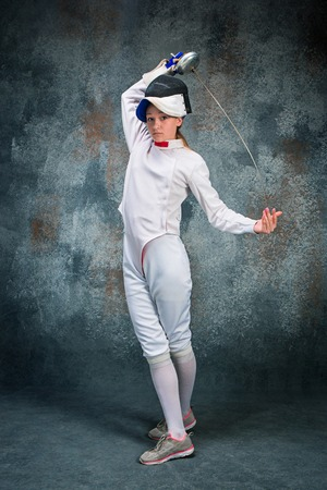 The woman wearing fencing suit with sword against gray Stock Photo