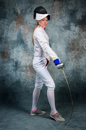 esgrimista: The woman wearing fencing suit with sword against gray Foto de archivo