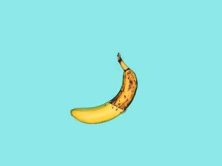 Single banana against blue background