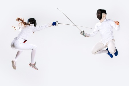 protective suit: The woman and man wearing fencing suit practicing with sword against gray