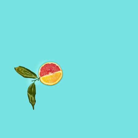 Grapefruit and orange citrus fruit halves on blue