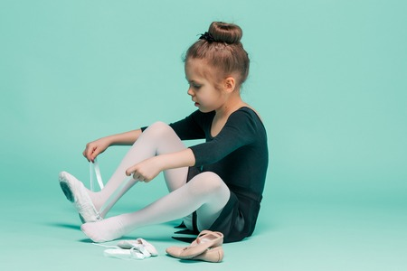 Beautiful little ballerina in black dress for dancing puting on foot pointe shoes Stock Photo